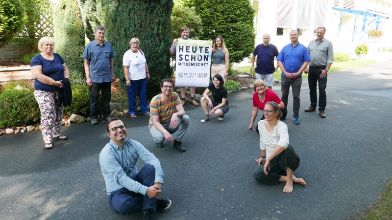 Vertreter*innen der Partnerschaften für Demokratie halten das Plakat der Kampagne